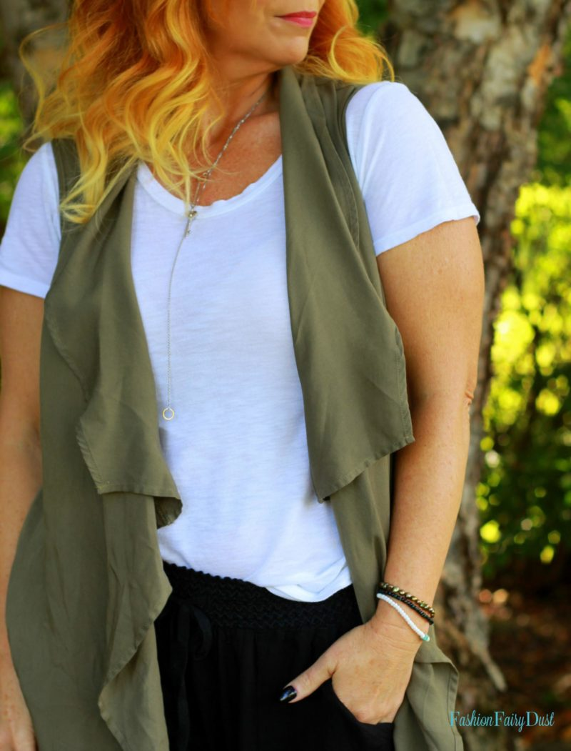 Long olive vest, Adidas Superstars and black slouchy pants. Casual outfit inspiration.