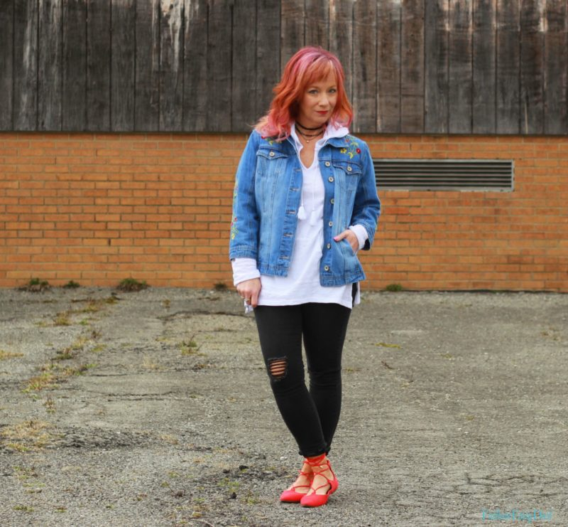 Embroidered denim jacket, white hoodie and black skinny jeans.