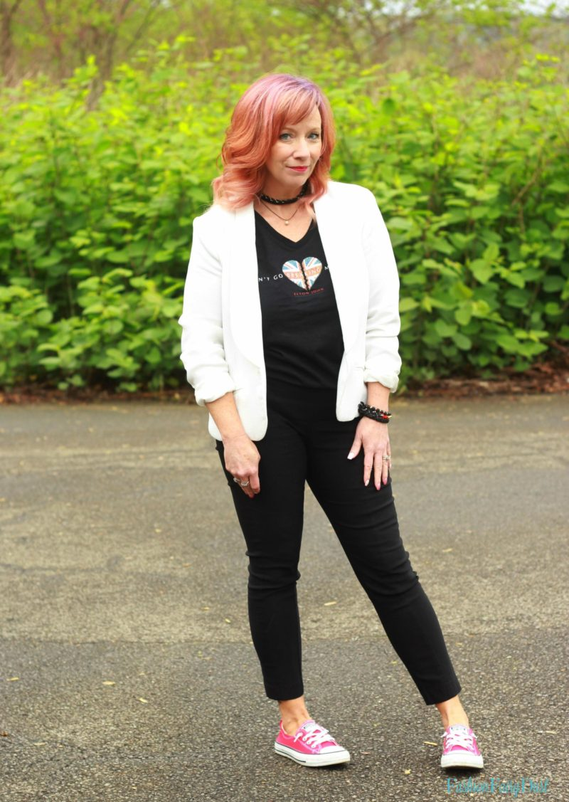 White blazer, graphic tee and black skinny pants.