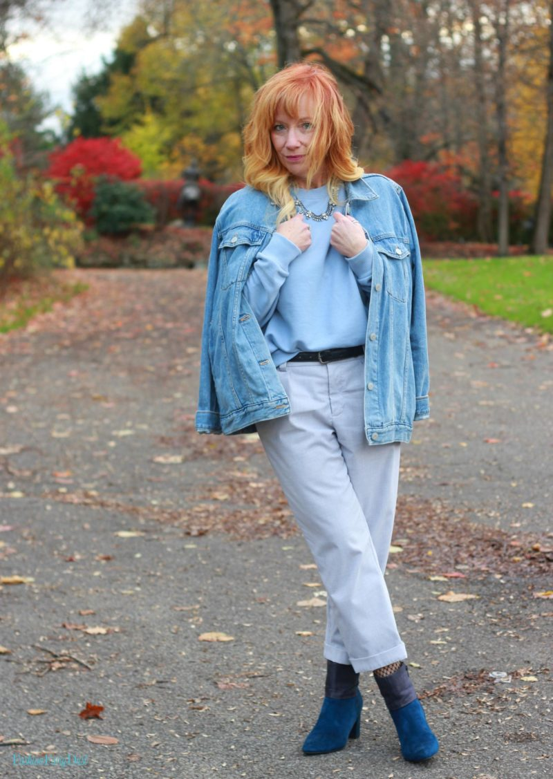 Ruffle sleeve sweatshirt, blue suede boots and gray pants.